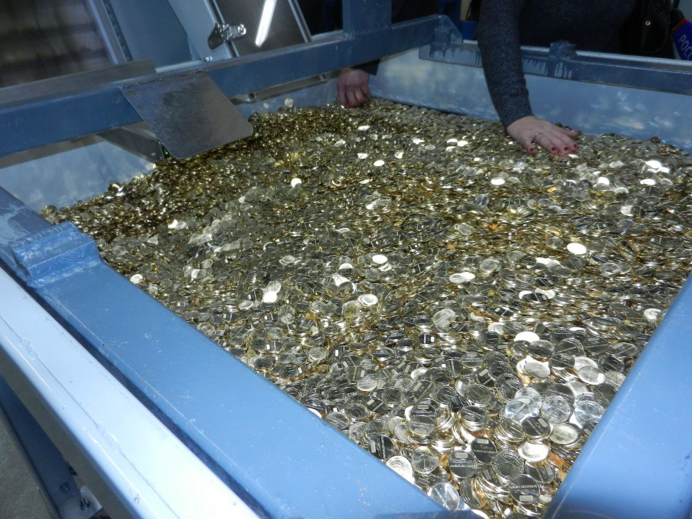 Из конвейера готовые жетоны летят прямо в огромный резервуар, который заполняется доверху. Интересно, на сколько поездок в метро хватит такого чана?