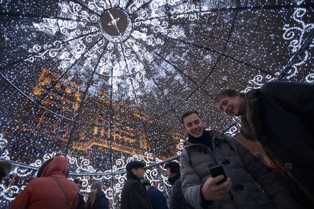 Москвичи фотографируются внутри гигантского елочного шара высотой 11, 5 метра, который установлен на Манежной площади.
