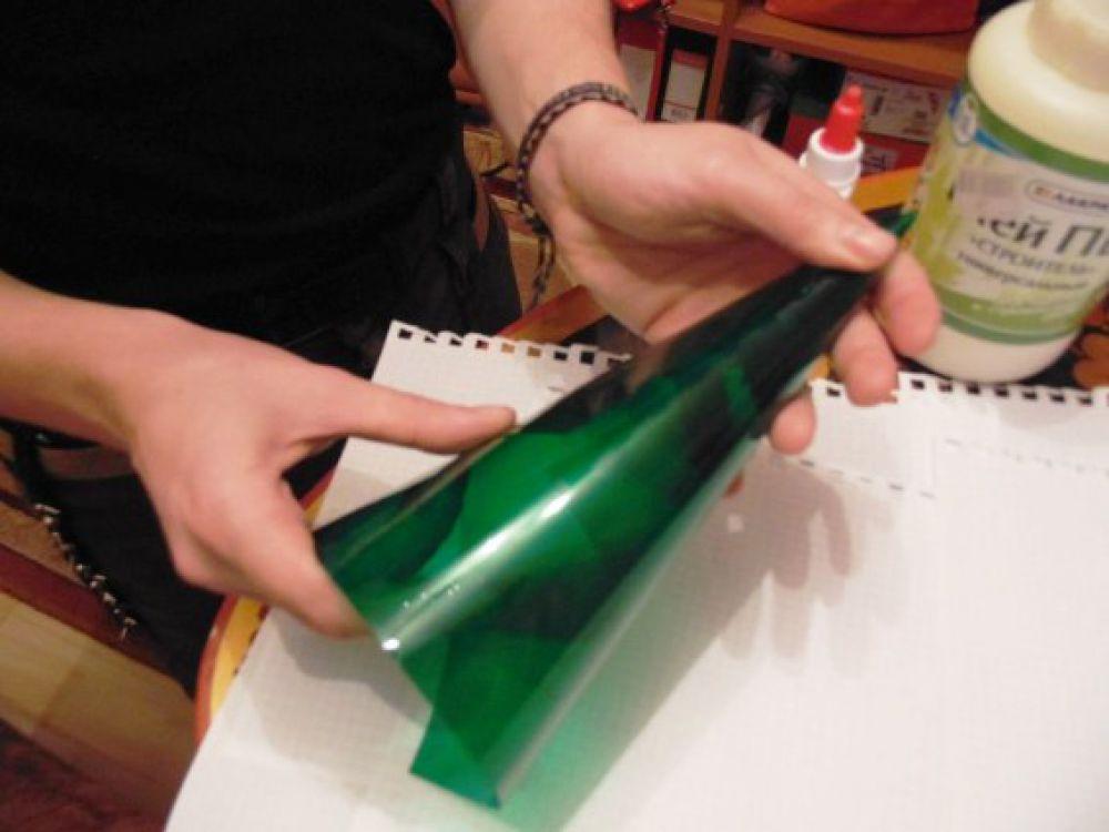Сворачиваем основу для елочки в форме конуса, скрепляя ее скотчем. Если это пластик, то переходим ко второму шагу. А если картон, то лучше конус дополнительно «ламинировать» скотчем, чтобы к нему не прилипал клей