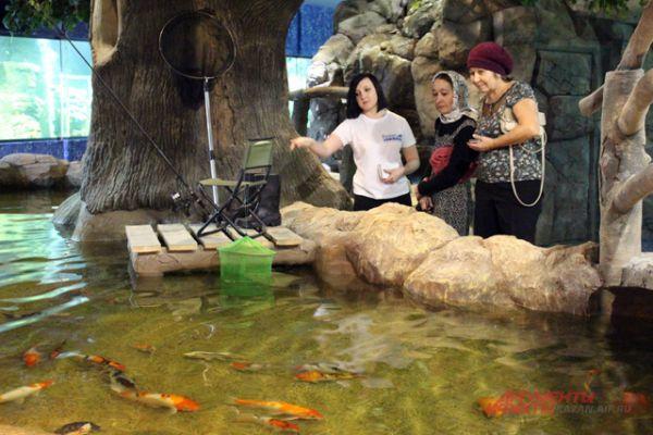 Экскурсовод объясняет посетителям особенности здешних рыб.