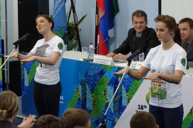 Волонтёры Лидия Дрёмова и Ксения Чучелина разучивают с аудиторией песню на языке жестов.