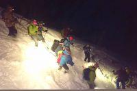 Группа горнолыжников спускает вниз пострадавшего товарища.