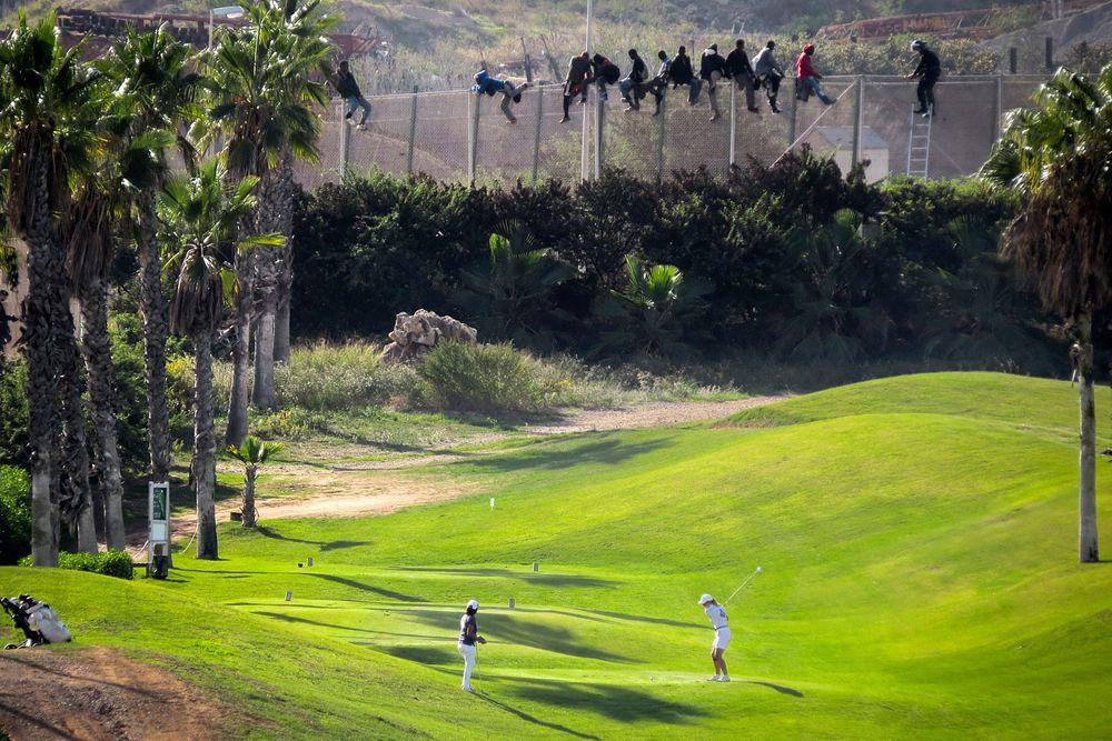 Африканские мигранты пытаются пересечь границу между Марокко и испанским автономным городом Мелилья.