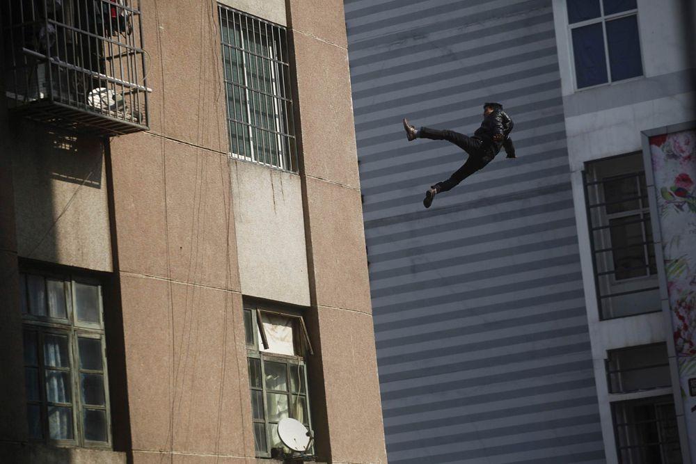 Лючжоу, Китай. Мужчина сорвался с крыши здания в тот момент, когда его пытались оттащить от края.