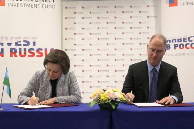Наталья Комарова и Кирилл Дмитриев подписывают соглашение.