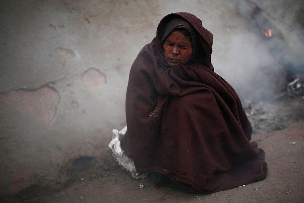 Женщина в лоскутном одеяле в старам квартале Дели.