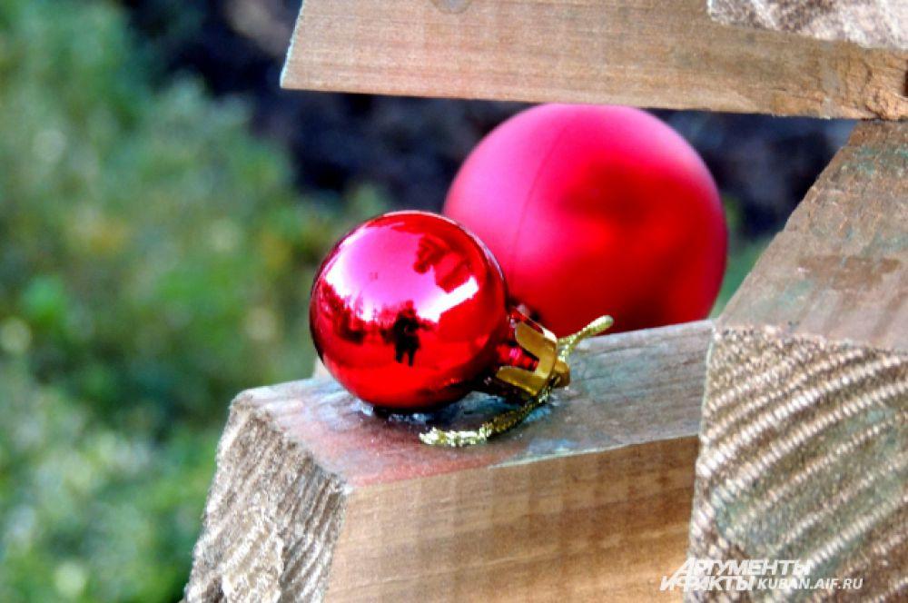 Деревянная елка украшена блестящими шарами.