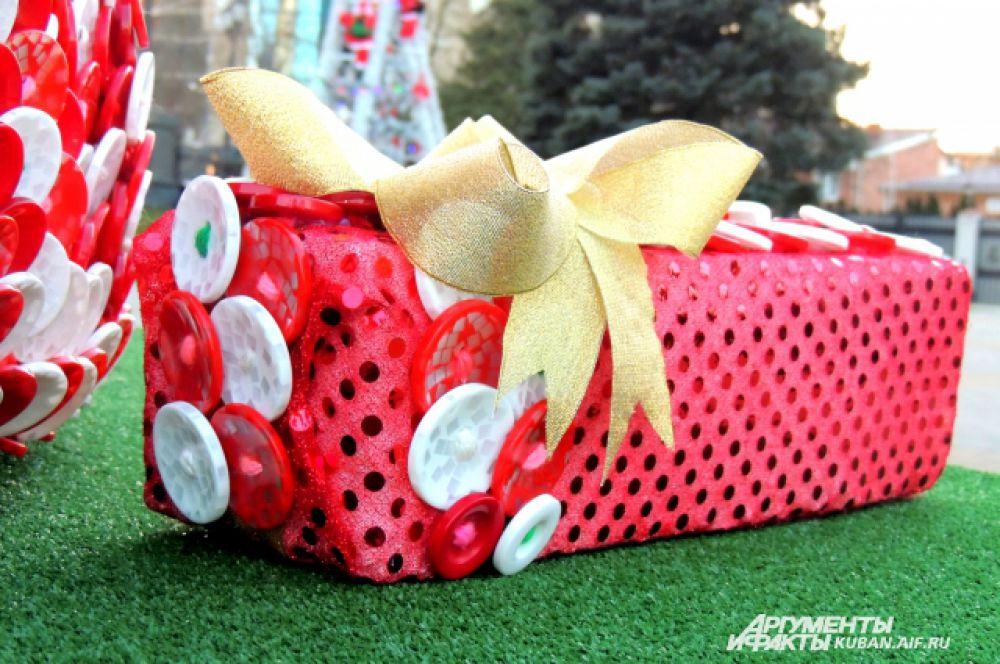 Под каждой елкой лежат подарки-муляжи.