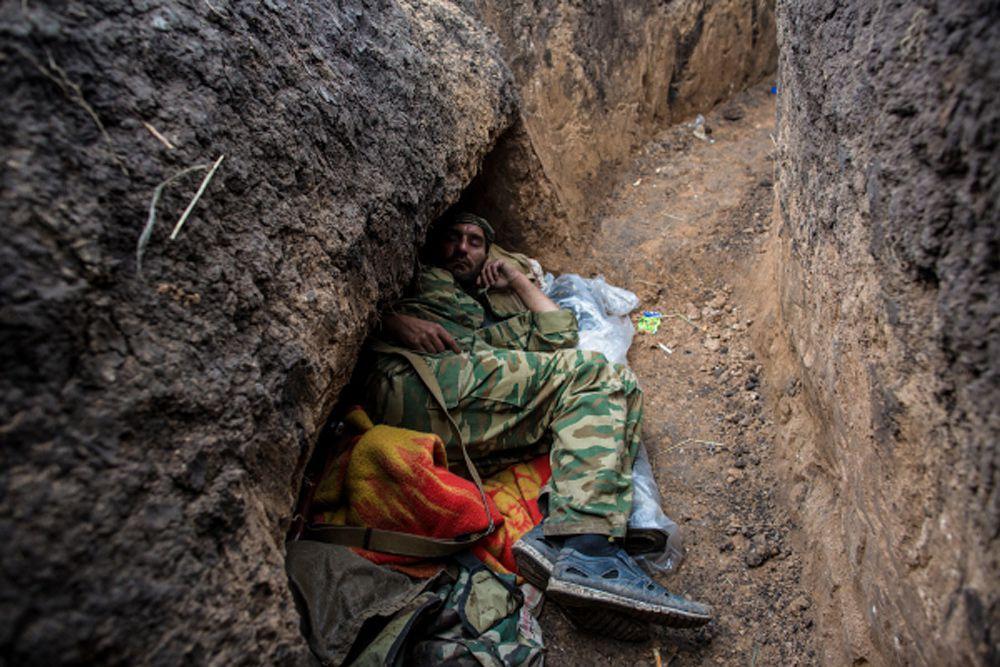 Ополченец отдыхает в траншее на передовой позиции в поселке Семеновка.
