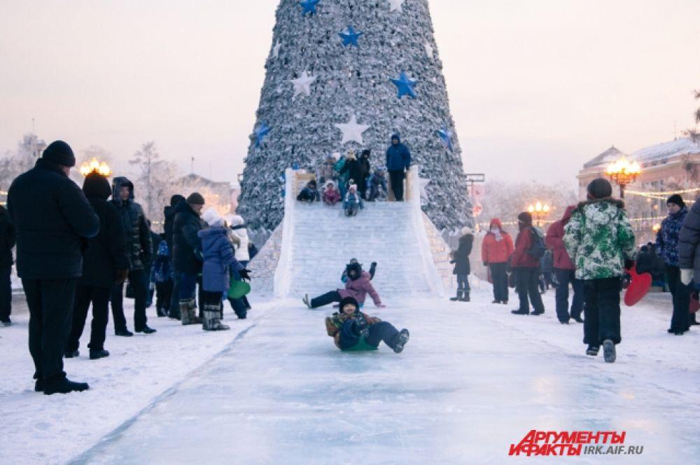 Так иркутская ель выглядит днем, когда народ катается на ледовых горках, устроенных на площади.