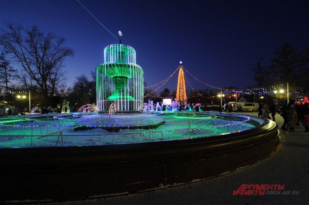 В Омске городская ель очень удачно смотрится на фоне комплекса фонтанов.
