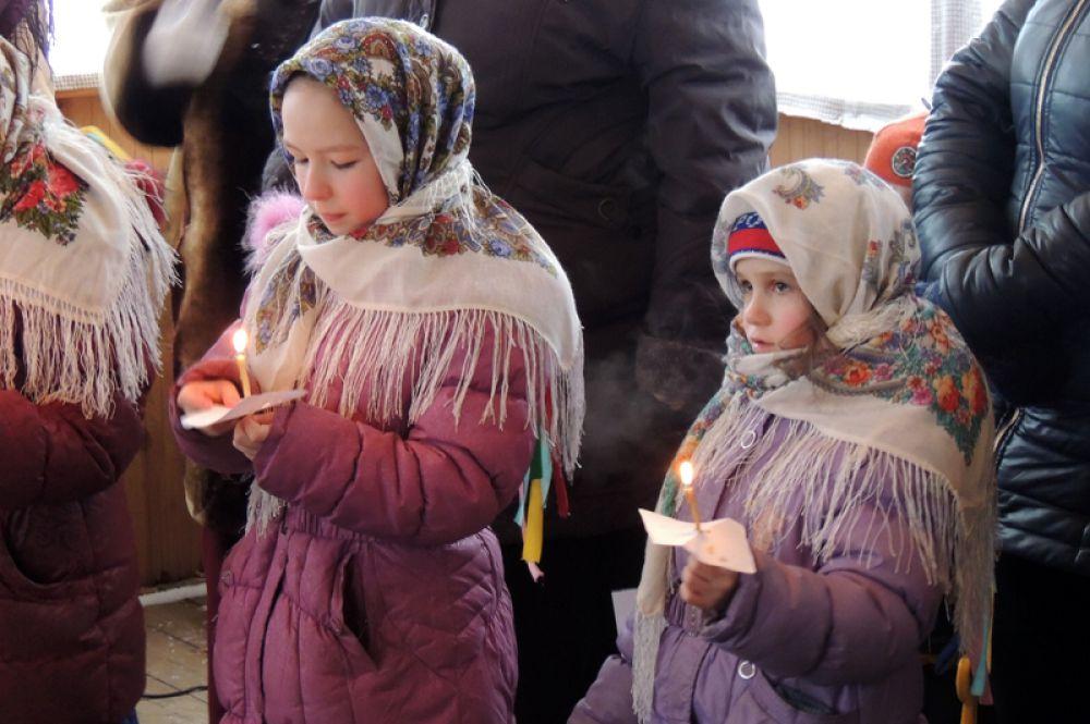 Рождественские песни поют со свечами.