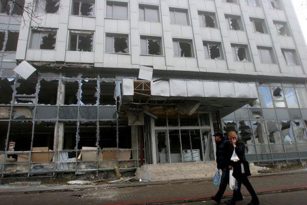 Горожане проходят мимо разрушенного в результате артобстрела украинскими военными здания в Донецке.