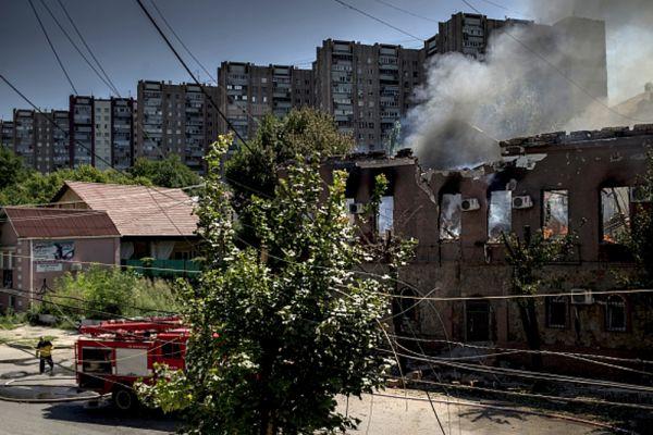 Пожар в здании, загоревшемся в результате попадания снаряда во время артиллерийского обстрела Луганска украинскими силовиками.