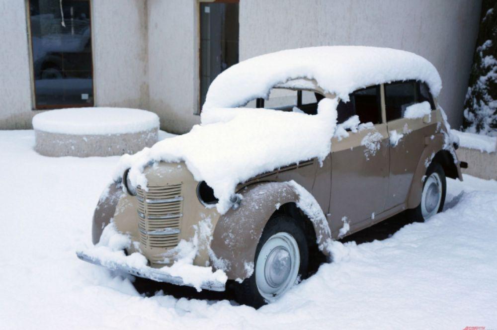Снег ложится белым покрывалом на крыши домов, дороги и автомобили.