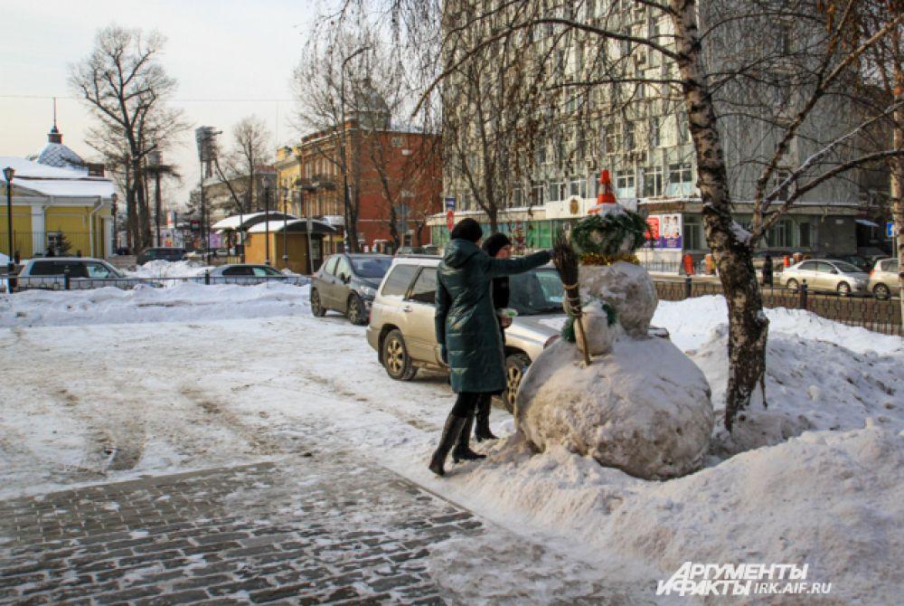 Горожане с удовольствием разглядывают снеговиков и фотографируют.