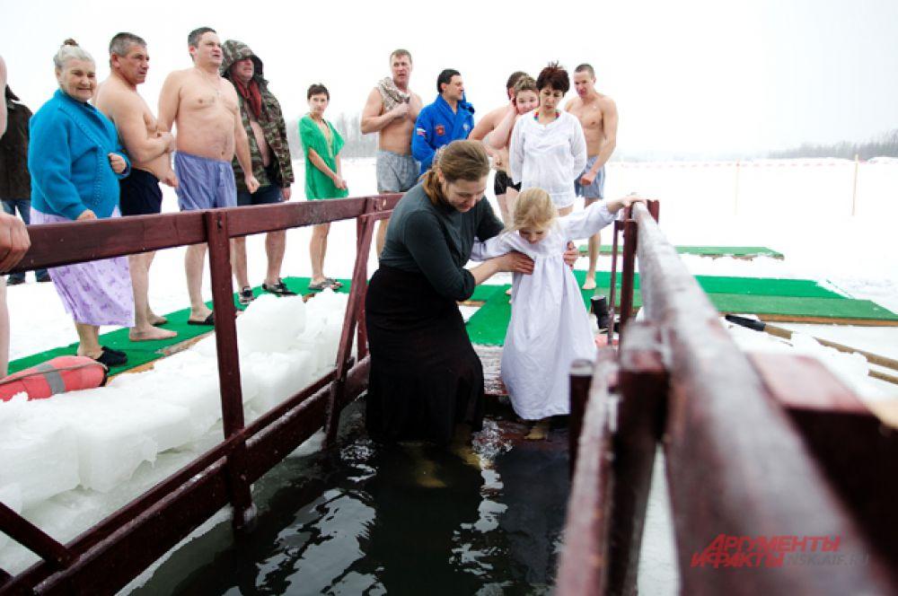 Дети редко заходят в крещенские купели, но девочка при поддержке мамы самостоятельно окунулась по пояс в воду
