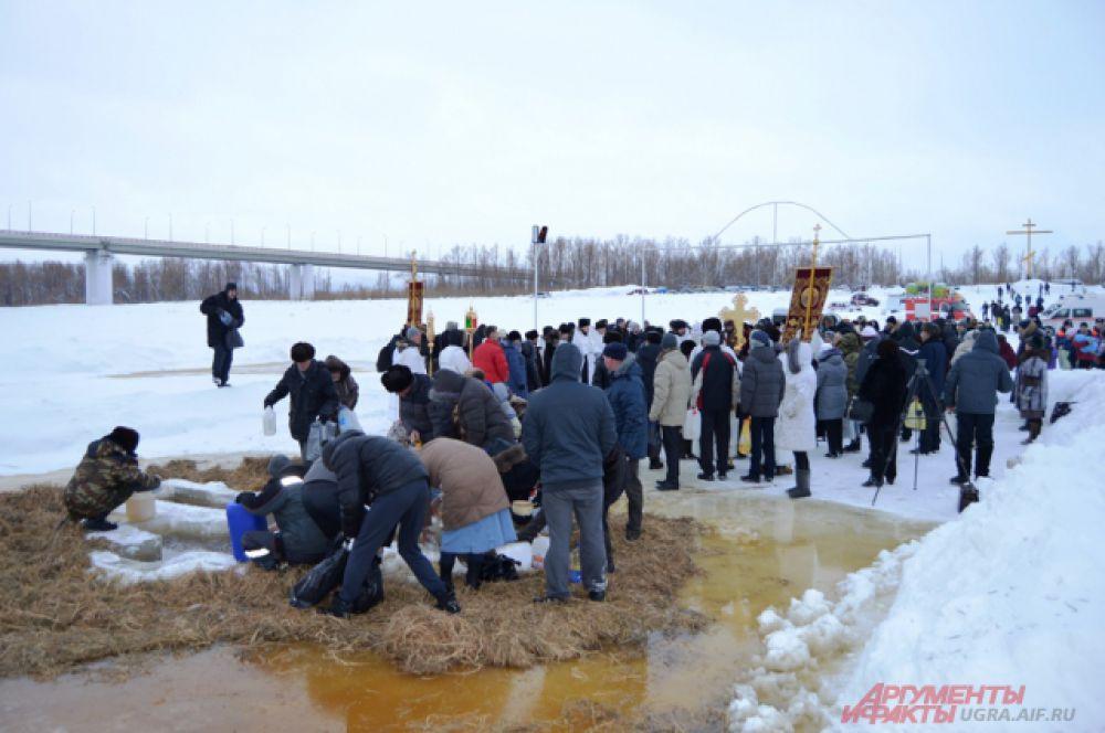 Те, кто не рискнул совершить крещенское омовение, набирают освященную воду из проруби.