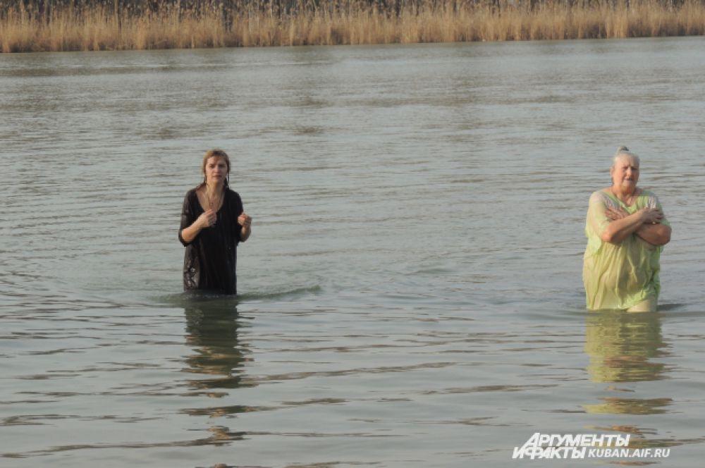Вслед за мужчинами в воду идут женщины.