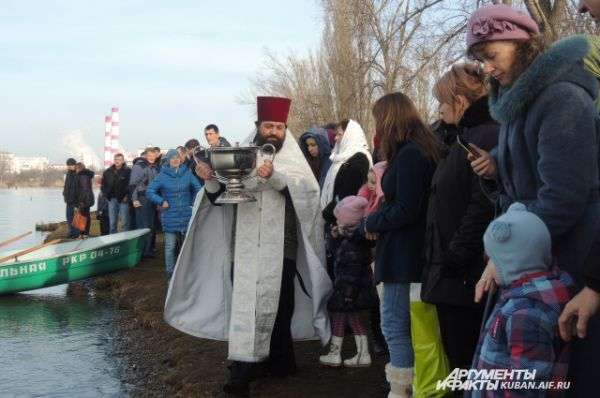 Отец Василий несет кубок с речной водой.