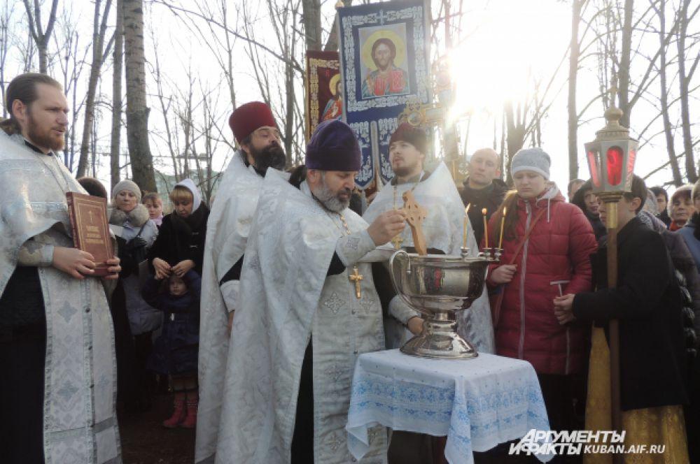 Протоиерей Александр омывает крест в уже окропленной воде.