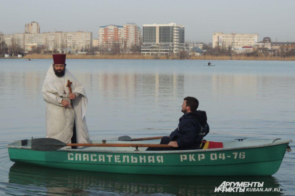 Отец Василий садится в лодку спасателей и освещает воду.