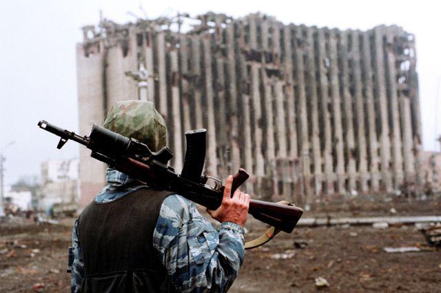 Боец с автоматом на плече стоит недалеко от разрушенного президентского дворца.