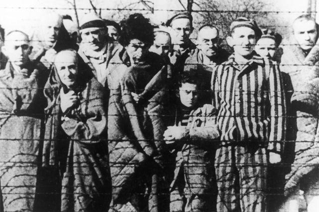Заключенные концлагеря Освенцим смотрят в объектив из-за колючей проволоки. Январь 1945 год.