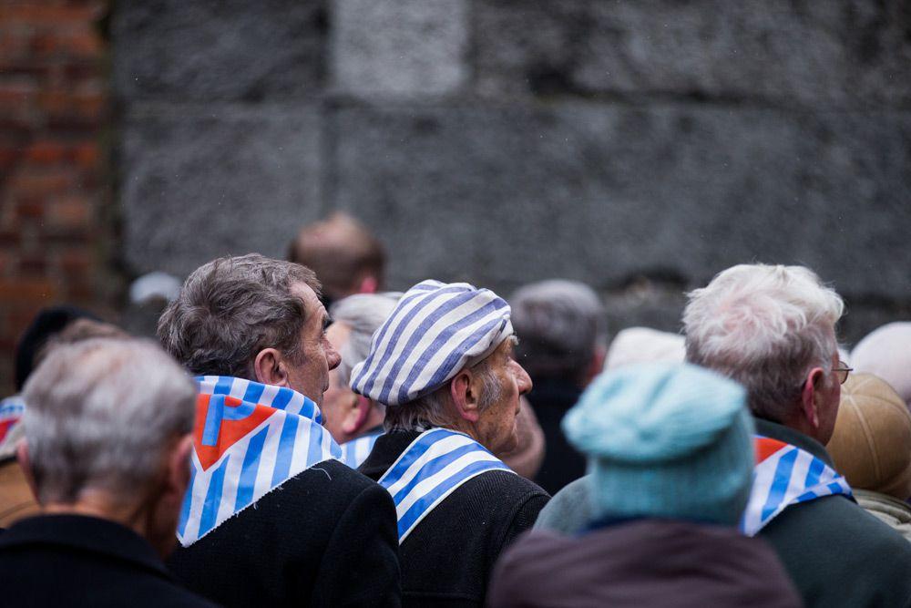 Некоторые бывшие заключенные на церемонии были одеты в характерные шапочки и робы в бело-синюю полоску, напоминающие о лагере, у других на шеи были повязаны полосатые платки.