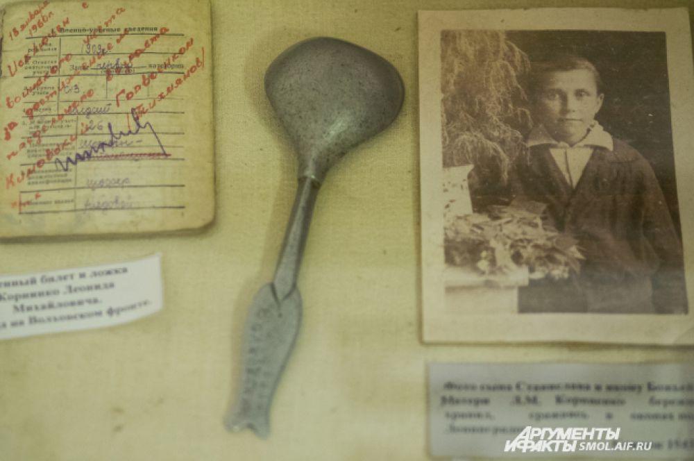 Рядом с землей находятся военный билет, медаль и ложка с нацарапанной надписью «Волховский фронт», принадлежавшие ветерану и участника войны Леониду Михайловичу Корниенко. Он работал шофером на дороге жизни.