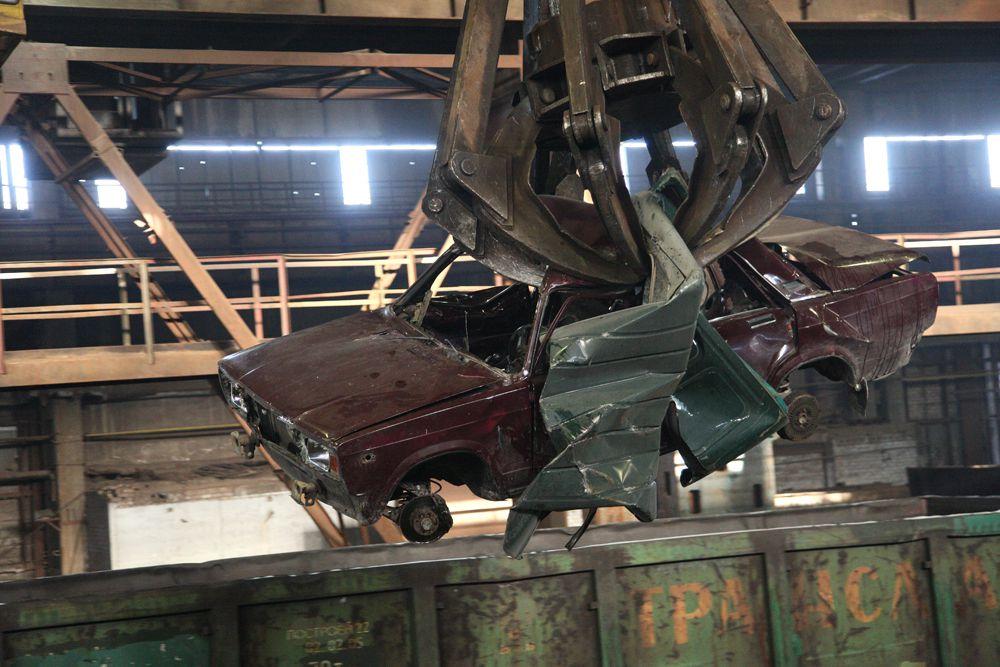 Железные «клешни» укладывают машину под пресс вместе с другим ломом.