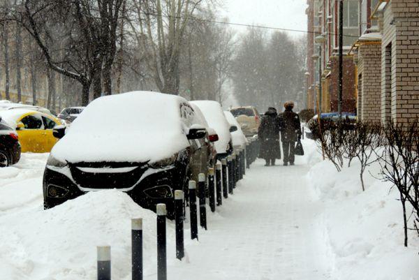 Машины едва видны под глубоким слоем снега.