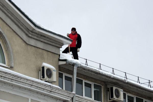 Снег приходится сбрасывать с крыш домов.