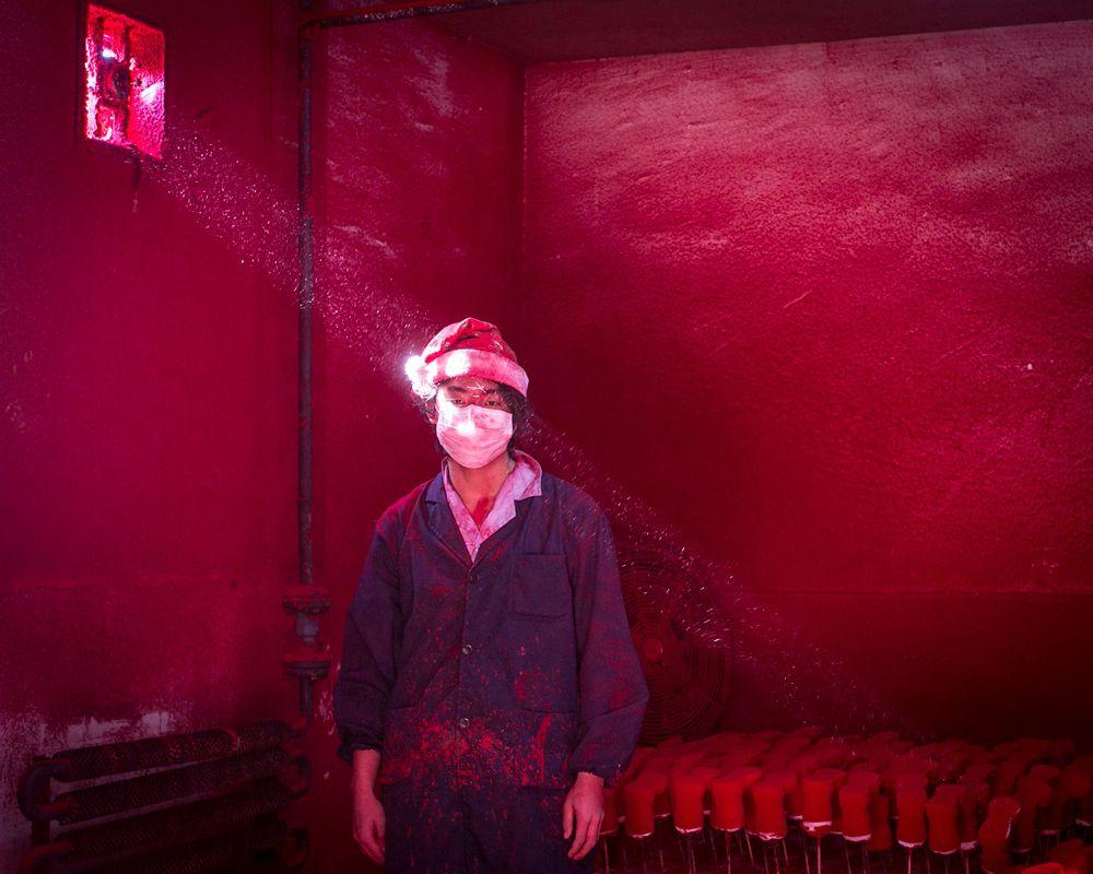Рангхуи Чэнь, китайский фотограф из City Express, занял второе место в категории «Современные проблемы». На его фотографии Вэй, 19-летний китайский рабочий в маске и шляпе Санты стоит рядом с рождественскими украшениями, а в воздухе парит порошок, используемый для окрашивания игрушек.