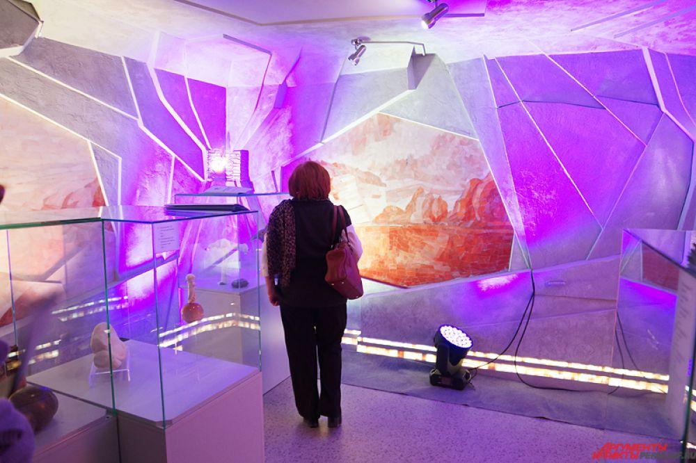 Произведения художников размещены на стеклянных стендах, а обрамляет композицию настенные декоративные панно из селенита различных оттенков