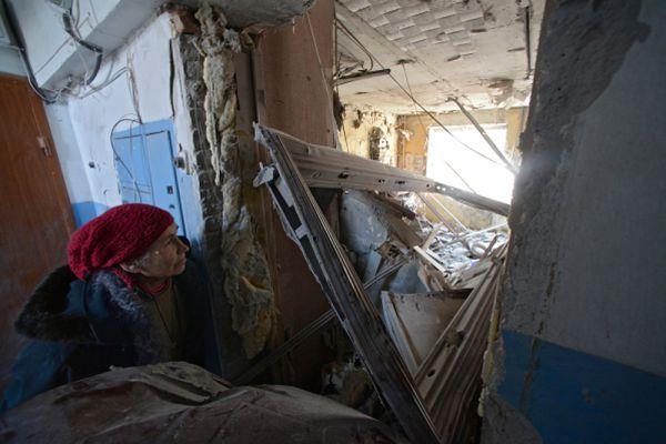 Женщина смотрит через заваленный вход на квартиру, разрушенную в результате обстрела Донецка.