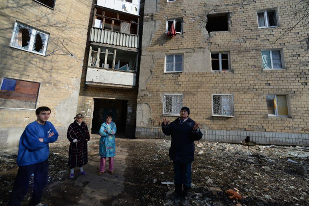 Жители Донецка во дворе дома, пострадавшего в результате обстрела города.