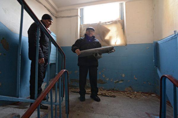 Мужчина достает часть снаряда из квартиры, разрушенной в результате обстрела Донецка.