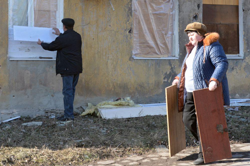 Жители дома ремонтируют окна, выбитые в результате обстрела Донецка.