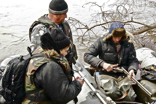 Инспекторы проверяют у охотника оружие и лицензию на отстрел.