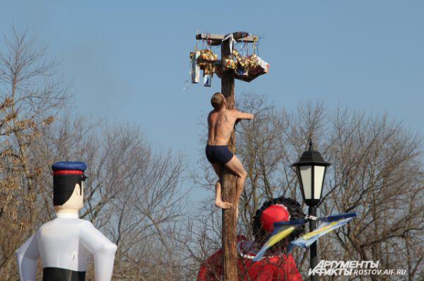 К обеду народ, наевшись блинов и шашлыков, стал шалить цирковыми номерами. Один смельчак полез по высоченному столбу за подарком.