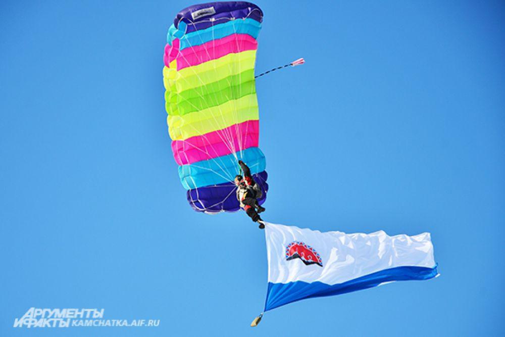 Красочное шоу парашютистов. Спортсмены спускались с неба с символикой гонки, великой Победы и Камчатского края.