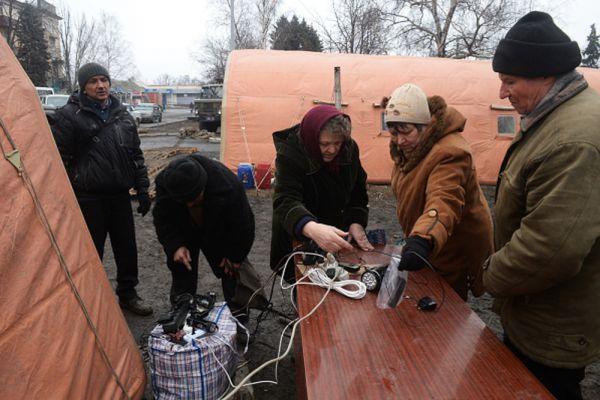 Жители Дебальцево заряжают мобильные телефоны от генератора МЧС.