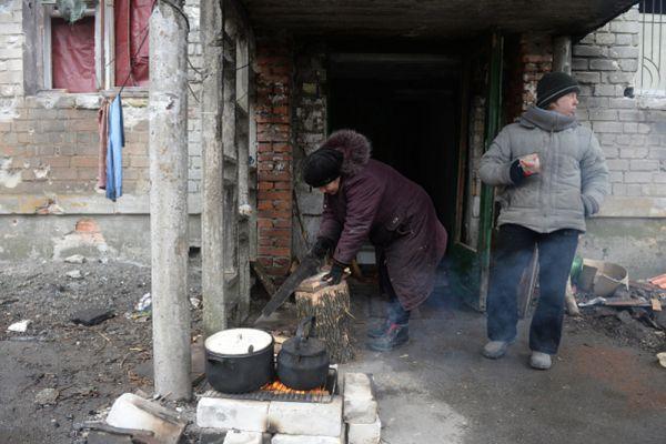 Жители Дебальцево готовят еду на костре у подъезда жилого многоквартирного дома, пострадавшего в результате обстрелов во время боевых действий.