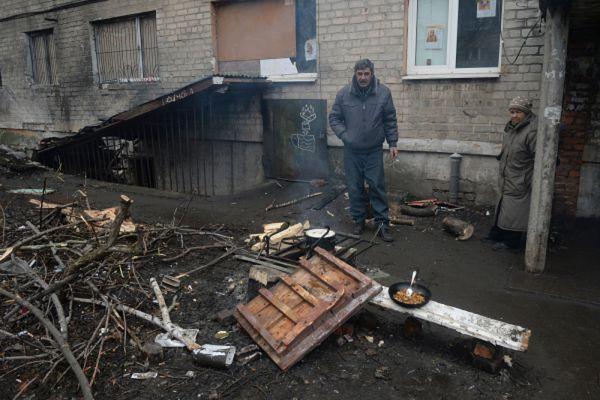Житель Дебальцево готовит еду на костре у подъезда жилого многоквартирного дома, пострадавшего в результате обстрелов во время боевых действий.