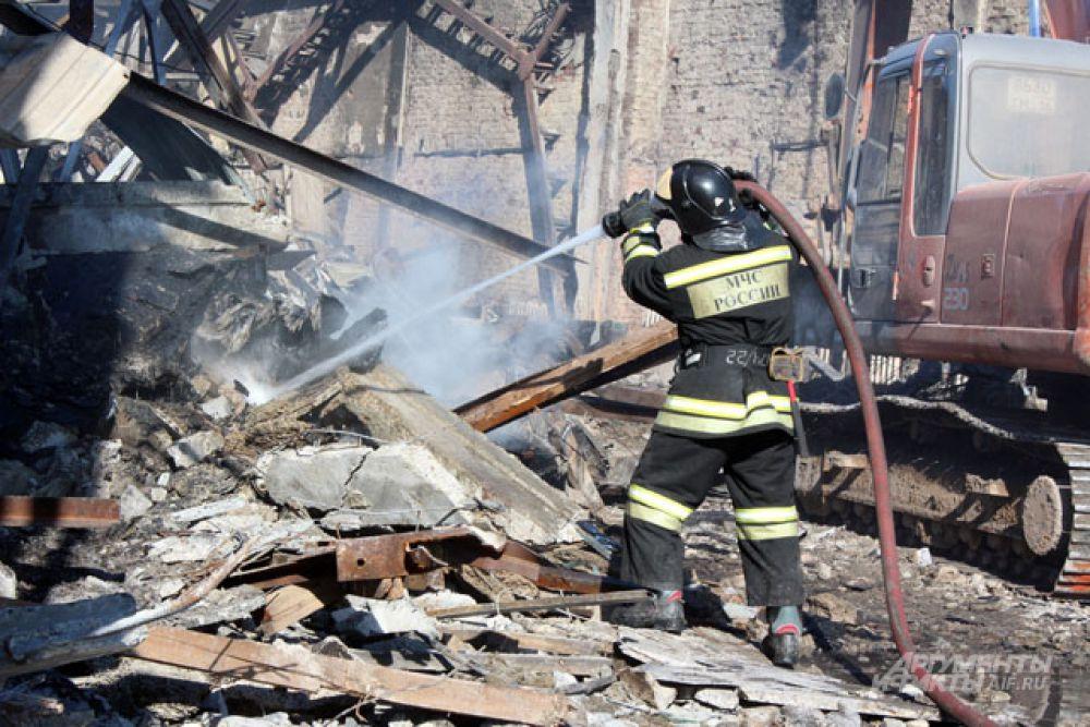 В некоторых местах завалы дымятся, пожарные поливают их водой.