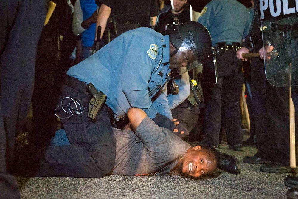 11 марта. США. Полицейский надевает наручники на человека, который протестовал против произвола полиции в городе Фергюсона.