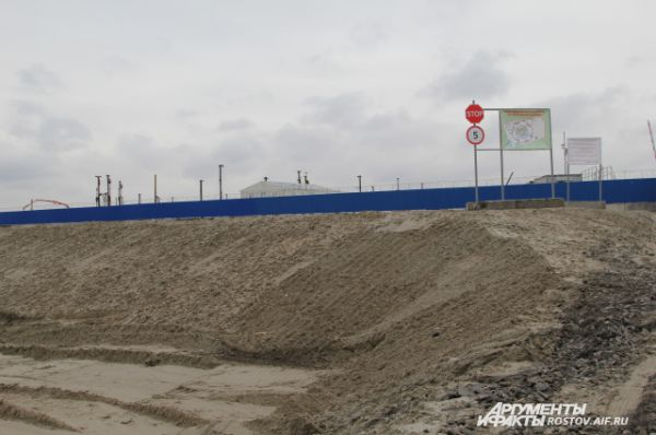 С улицы Левобережной виден синий забор стройки.