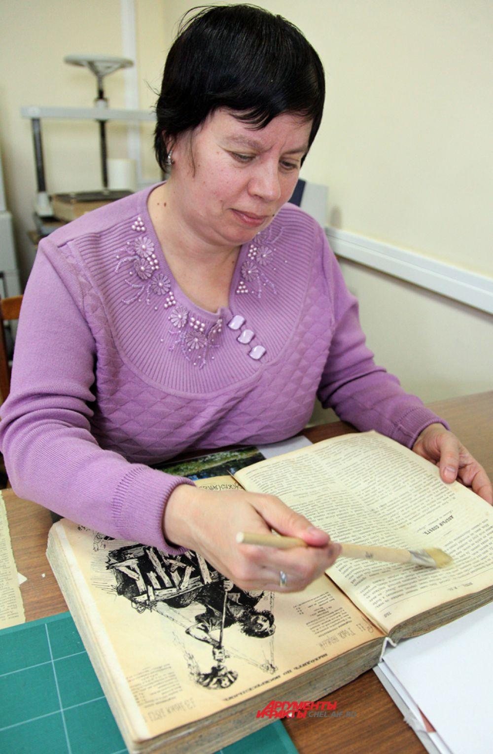 Механическую очистку редкой книги проводит реставратор Медведева О.Н.