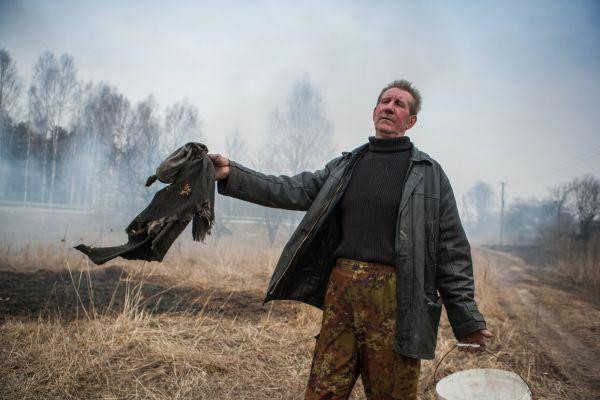 Житель Ново-Николаевского держит огонь под контролем с пустым ведром и мокрой тряпкой.